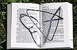 glasses-on-opened-book-10058125
